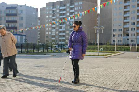Слепая девушка с палочкой идет по улице