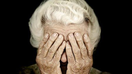 Пожилая женщина закрыла глаза руками