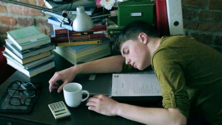 Парень устал и спит на столе с книгами