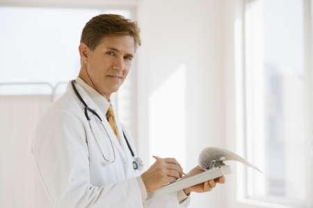 Мужчина-врач записывает что-то в блокнот