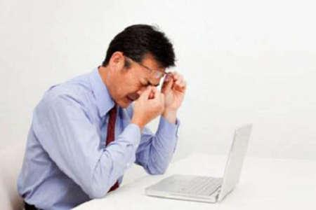 Мужчина устал работать за компьютером, трет глаза