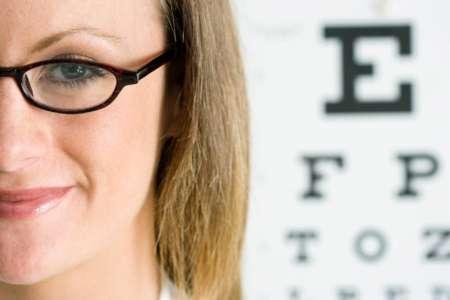 Женщина в очках на фоне таблицы для проверки зрения