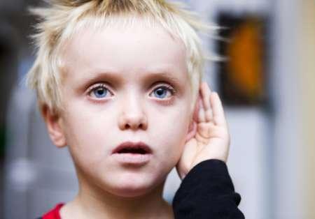 ребёнок прижимает руку к уху