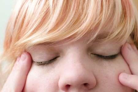 Девушка с закрытыми глазами массажирует уголки глаз