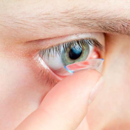 Мужчина надевает контактные линзы