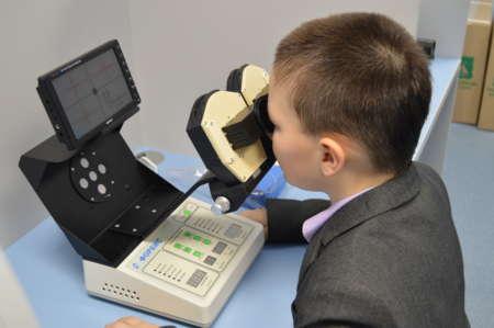 мальчик занимается на специальном аппарате для коррекции зрения