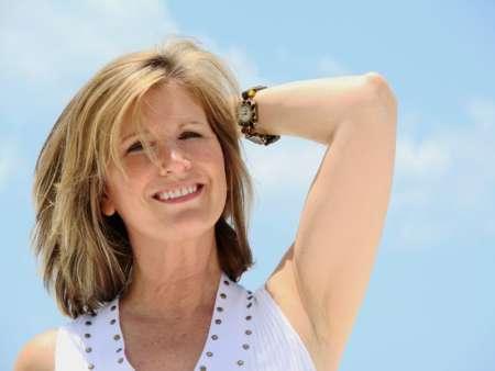 Женщина улыбается на фоне голубого неба