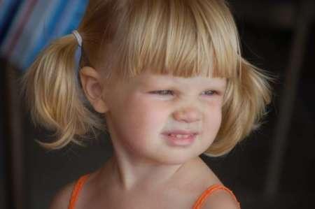 Девочка морщит лицо