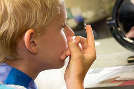 Ребенок надевает контактные линзы