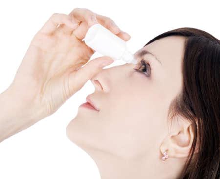 Девушка закапывает глаза глазными каплями