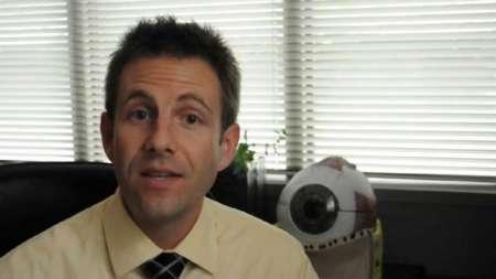 Мужчина на фоне макета глазного яблока