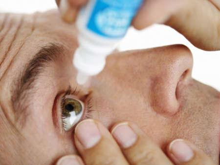 Мужчина капает глаза глазными каплями
