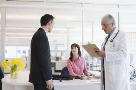 Пациент в регистратуре записывается на прием к врачу