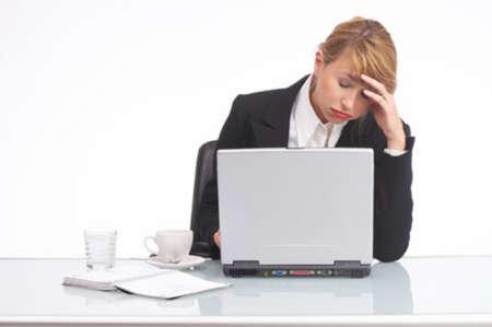 Женщина устала работать за компьютером, держится за голову