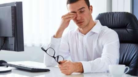 Мужчина за компьютером трет глаза устал