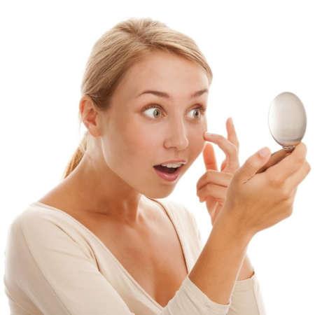 Удивлённая девушка рассматривает лицо в маленьком зеркальце