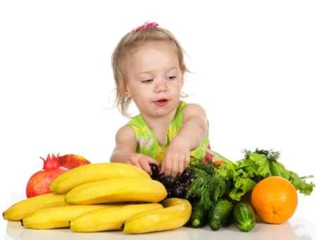 Малышка смотрит на овощи и фрукты