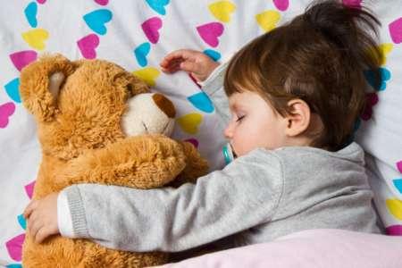 Ребёнок спит с игрушечным медведем в обнимку.