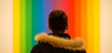 мужчина напротив разноцветных обоев